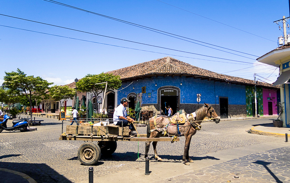 Granada, Nicaragua: colorful street with horse carriage